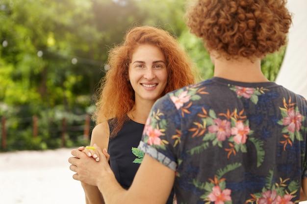 Heureuse femme aux taches de rousseur dansant à l'extérieur avec son petit ami