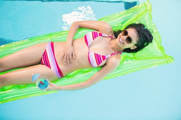 Heureuse femme en bikini allongé sur un lit d'air dans la piscine
