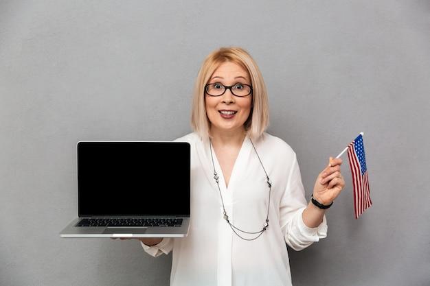 Heureuse femme blonde d'âge moyen en chemise et lunettes