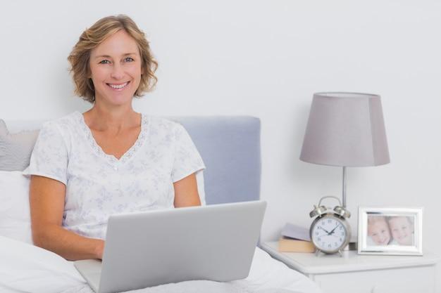 Heureuse femme blonde assise dans son lit à l'aide d'un ordinateur portable