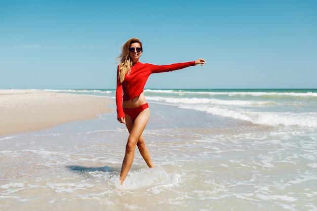 Heureuse femme blonde au bord de la mer souriant heureux. concept de vacances d'été. amzing plage tropicale. porter un bikini rouge. corps bronzé parfait et silhouette élancée.