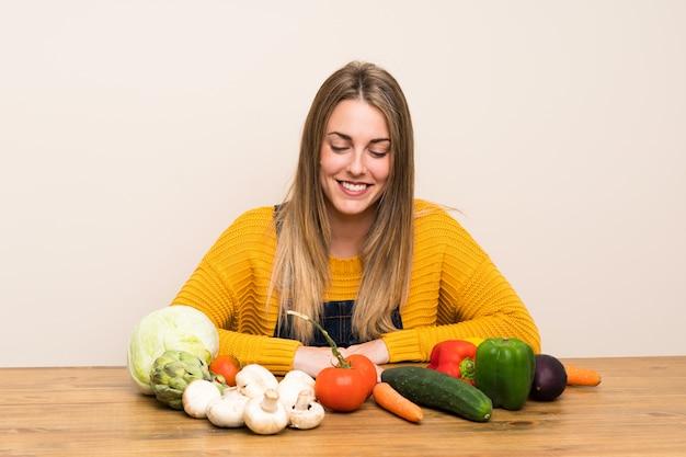 Heureuse femme blonde avec beaucoup de légumes