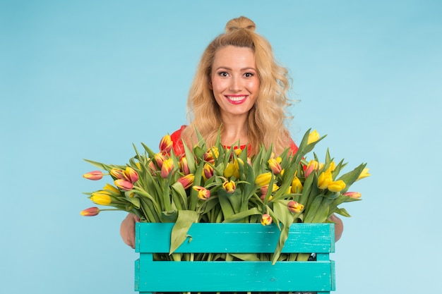 Heureuse femme blonde caucasienne fleuriste en riant et tenant une grande boîte de tulipes sur fond bleu