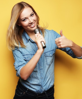 Heureuse femme blonde chantant dans le microphone sur l'espace jaune
