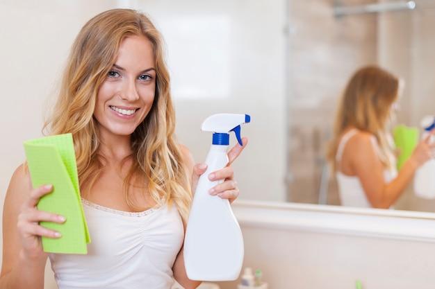 Heureuse femme blonde est prête à nettoyer la salle de bain