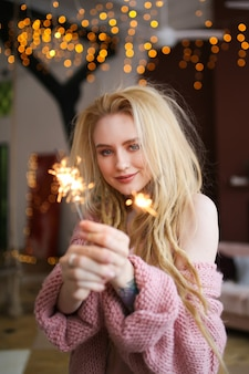 Heureuse femme blonde joyeuse fête le nouvel an par l'arbre de noël