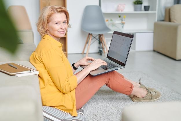 Heureuse femme blonde mature avec ordinateur portable sur ses genoux assis sur le sol et effectuant des points de travail pendant le travail à distance en quarantaine