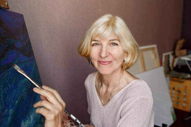 Heureuse femme blonde mature peinture sur toile à la maison