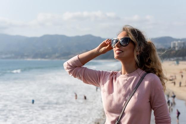 Heureuse femme blonde à la plage de los angeles