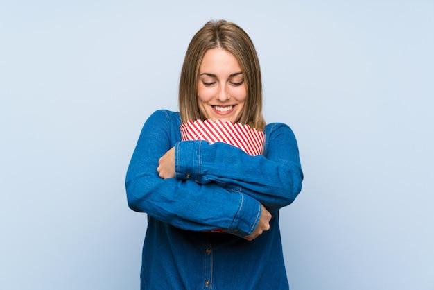 Heureuse femme blonde avec des pop-corn sur le mur bleu