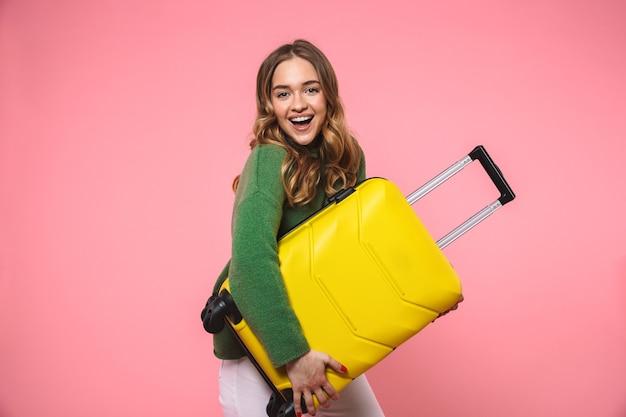 Heureuse femme blonde portant un pull vert tenant des bagages et regardant l'avant sur le mur rose