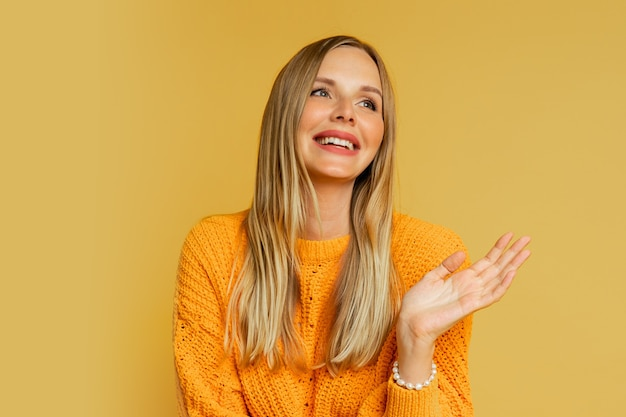 Heureuse femme blonde en pull d'automne élégant orange posant sur jaune.