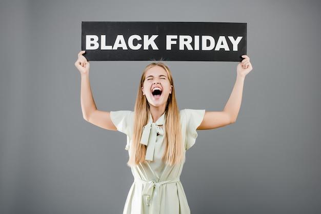 Heureuse femme blonde qui crie avec signe de vendredi noir isolé