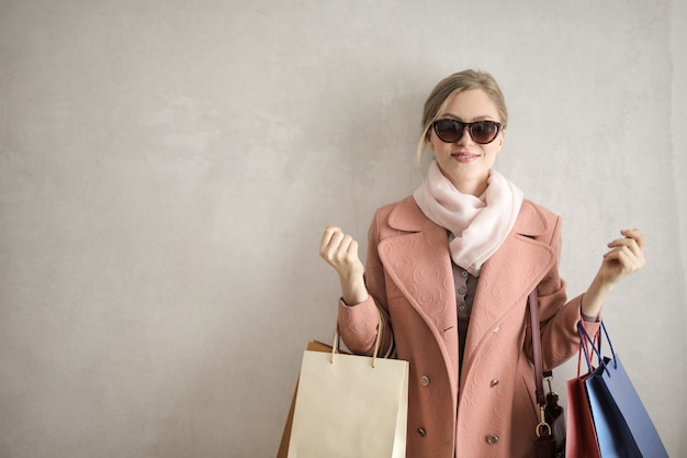 Heureuse femme blonde avec des sacs à provisions