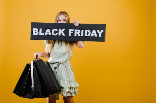 Heureuse femme blonde avec signe vendredi noir et papier sacs à provisions isolés sur jaune