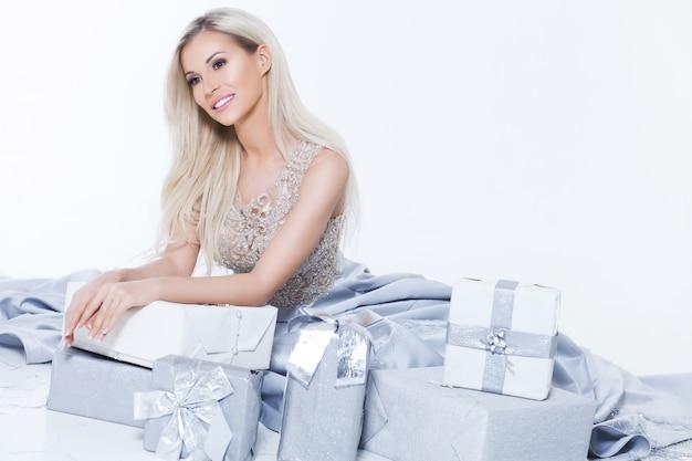 Heureuse femme blonde souriante en robe longue argent avec boîte-cadeau et chute de confettis au fond blanc isolé