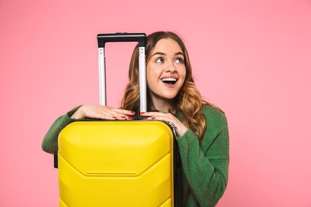 Heureuse femme blonde vêtue d'un pull vert posant avec des bagages et regardant loin par-dessus le mur rose