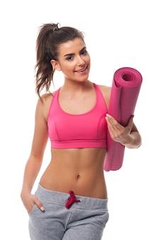 Heureuse femme en bonne santé avec tapis de yoga