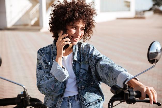Heureuse femme bouclée assise sur une moto moderne à l'extérieur et parlant par le smartphone