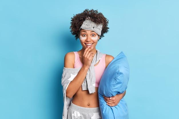 Heureuse femme bouclée surprise entend de bonnes nouvelles après le réveil étant intéressé par les sourires promotionnels tient largement le menton pose avec oreiller porte des vêtements de nuit isolés sur un mur bleu