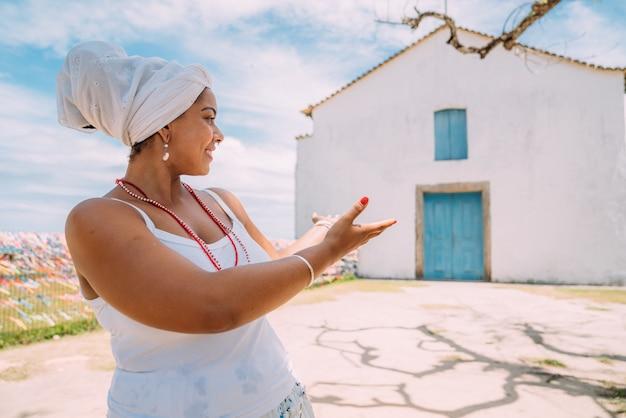 Heureuse femme brésilienne habillée en costume traditionnel bahianais montrant l'église avec la paume de sa main, regarde la caméra, avec le centre historique de porto seguro en arrière-plan
