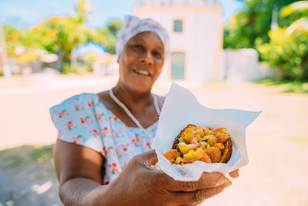 Heureuse femme brésilienne vêtue du costume traditionnel bahianais de la religion umbanda, offrant des acarajã © - cuisine typique de bahia - dans le centre historique de porto seguro en arrière-plan