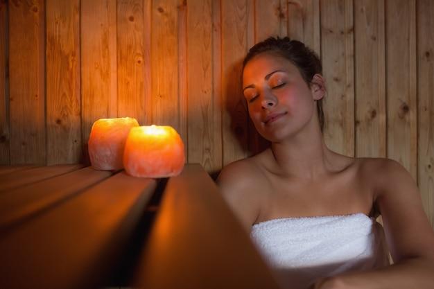 Heureuse femme brune assise dans un sauna