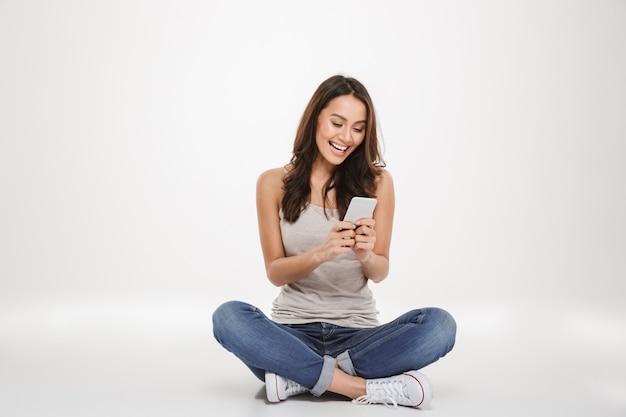 Heureuse femme brune assise sur le sol et écrit un message sur smartphone sur gris