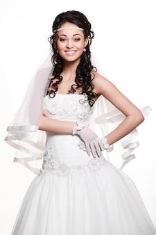Heureuse femme brune belle mariée sexy en robe de mariée blanche avec coiffure et maquillage lumineux