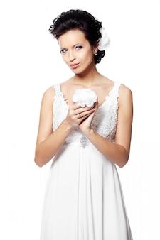Heureuse femme brune belle mariée sexy en robe de mariée blanche avec fleur en mains avec coiffure et maquillage lumineux avec fleur en cheveux isolé sur blanc