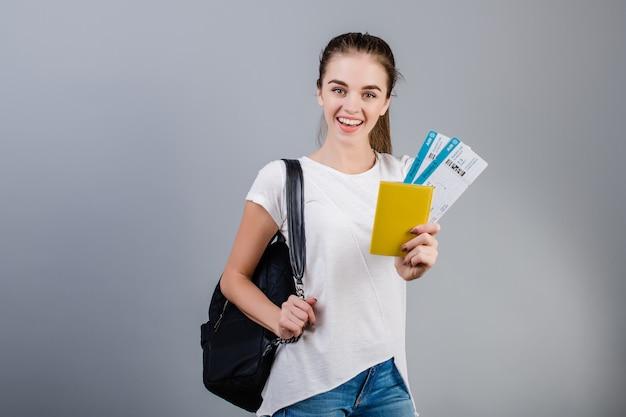 Heureuse femme brune avec des billets d'avion dans le passeport et sac à dos isolé sur gris
