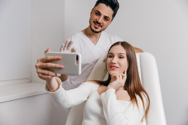 Heureuse femme brune à la clinique médicale de beauté. elle parle avec un médecin d'un traitement esthétique du visage.
