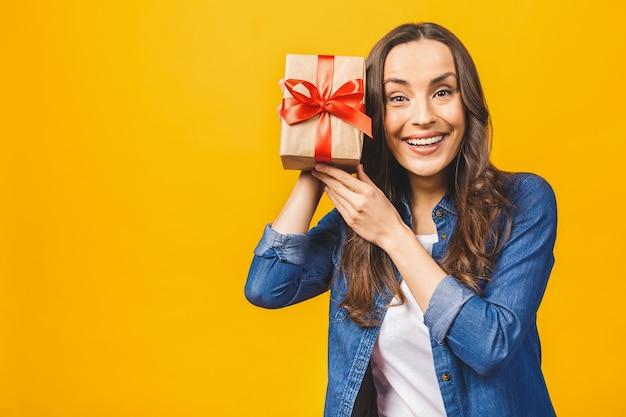 Heureuse femme brune dans une boîte-cadeau tenue décontractée