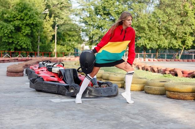 Heureuse femme brune gagnant la course de karting. jeune fille blonde en costume de sport rouge posant en été sur une piste de karting