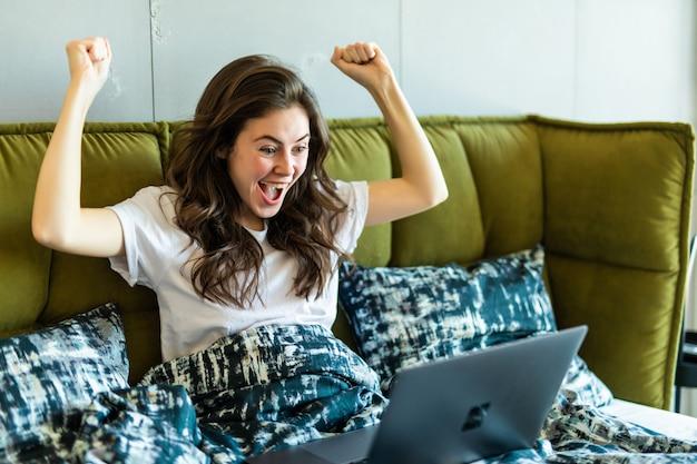 Heureuse femme brune avec un geste de victoire à l'aide d'un ordinateur portable assis sur le lit le matin