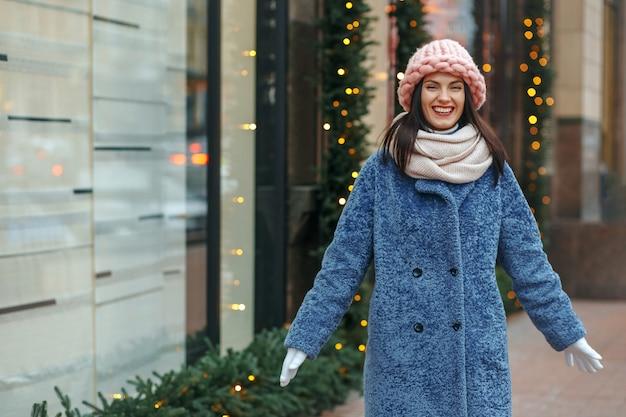 Heureuse femme brune en manteau profitant de l'hiver. espace libre