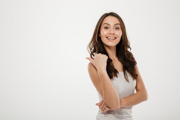 Heureuse femme brune pointant loin et regardant la caméra sur gris