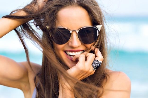 Heureuse femme brune porte une bague élégante en riant tout en posant en mer. portrait en gros plan d'une jeune fille bronzée à lunettes de soleil noires jouant avec ses cheveux noirs sur fond flou.