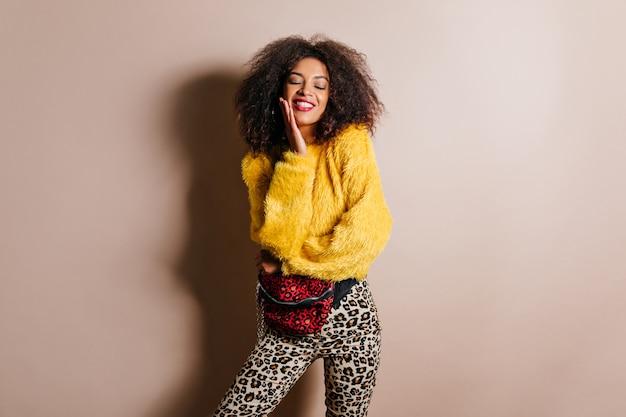 Heureuse femme brune posant avec un sourire sincère sur un mur beige