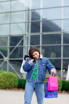 Heureuse femme brune avec des sacs à provisions et téléphone portable bénéficiant de shopping. shopping, concept de style de vie