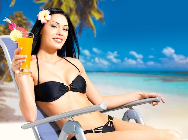 Heureuse femme brune en vacances à la plage
