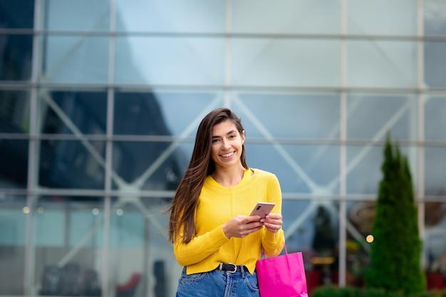 Heureuse femme brune vêtue d'un pull jaune, avec des sacs à provisions et un téléphone portable profitant du shopping.