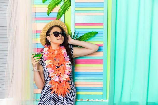 Heureuse femme buvant un cocktail vert à hawaii