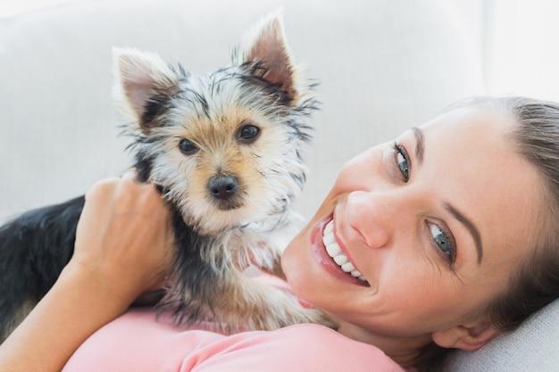 Heureuse femme câlins son yorkshire terrier sur le canapé