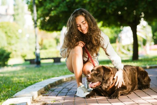 Heureuse femme caressant son chien dans le parc