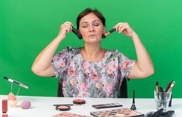 Heureuse femme caucasienne adulte assise les yeux fermés à table avec des outils de maquillage tenant des pinceaux de maquillage