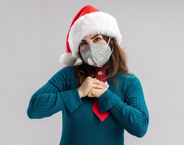 Heureuse femme caucasienne adulte avec bonnet de noel et cravate de noel portant un masque médical tient son poing isolé sur un mur blanc avec espace de copie