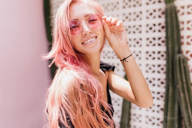 Heureuse femme caucasienne bronzée aux cheveux roses. heureuse dame européenne touchant ses lunettes de soleil tout en posant avec des plantes exotiques.