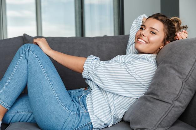 Heureuse femme caucasienne en chemise rayée souriante en position couchée sur le canapé du salon