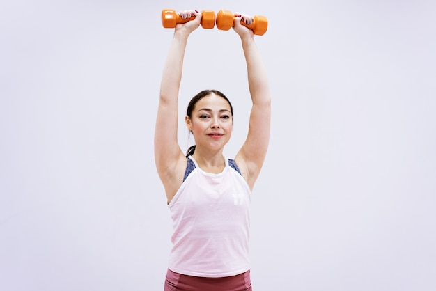 Heureuse femme caucasienne faisant du fitness avec des haltères à la maison sur fond de mur